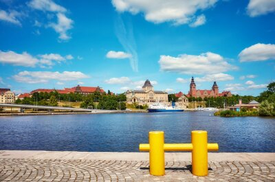 Szczecin waterfront with yellow mooring bollard in foreground, Poland.