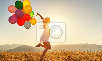 Obraz szczęśliwa kobieta z balonami o zachodzie słońca w lecie
