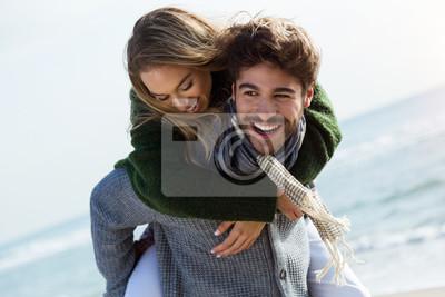 Obraz Szczęśliwa młoda para korzystających dzień w zimie zimno na plaży.