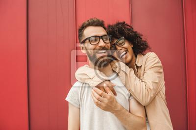 Obraz szczęśliwa młoda para wieloetniczna w okularach przytulanie na ulicy