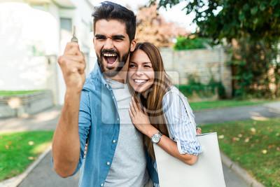 Obraz Szczęśliwa młoda para z kluczem w ręku stoi na zewnątrz przed ich nowym domu.