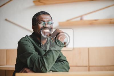 Obraz szczęśliwy dojrzały mężczyzna w kawiarni