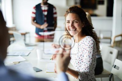 Obraz Szczęśliwy młody bizneswomanu obsiadanie przy biurkiem i komunikować z jej kolegami podczas spotkania