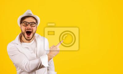 Obraz Szczęśliwy modniś wskazuje up na kolorze żółtym