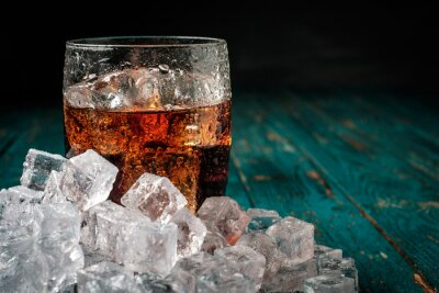 Obraz Szkło cola z lodem na drewnianym stole.