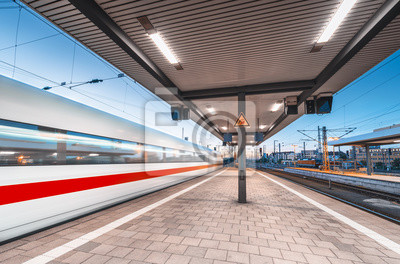 Szybki pociąg w ruchu na stacji kolejowej z pięknym oświetleniem w nocy. Poruszający zamazany nowożytny intercity pociąg na platformie kolejowej przy zmierzchem. Transport pasażerski. Popędzać