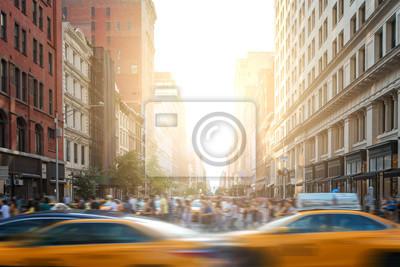 Szybki ruch w Nowym Jorku, gdy żółte taksówki przyspieszają zjazd na 5th Avenue z tłumami zapracowanych ludzi idących przez skrzyżowanie na 23rd Street na Manhattanie z zachodem słońca w tle