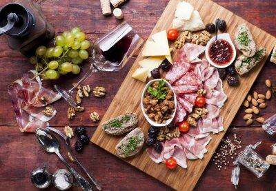Obraz Szynka, ser, winogrona, czerwone wino na drewnianym stole, widok z lotu ptaka