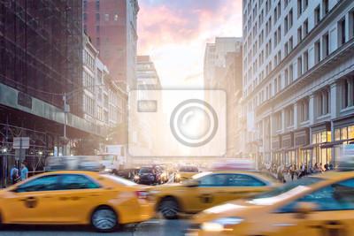 Taksówki w ruchu obok tłumów ludzi na Broadwayu z kolorowym zachodem słońca na Manhattanie w Nowym Jorku