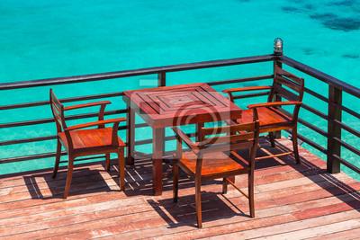 Taras z widokiem na morze z zewnątrz krzesła i stolik z drewna