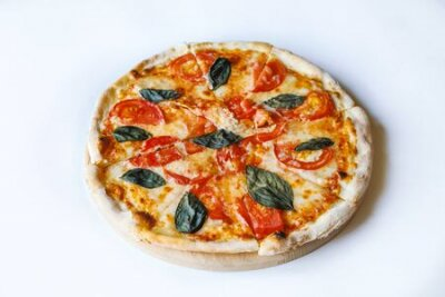 Obraz tasty vegetable pizza on desk board on white background
