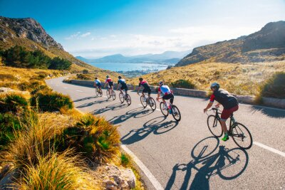 Obraz Team sport cyclist photo. Group of triathlete on bicycle ride on the road at Mallorca, Majorca, Spain.