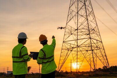 Obraz Team work of Engineers location help Technician use drone to fly inspections at the electric power station to view the planning work by producing electricity high voltage electric transmission tower