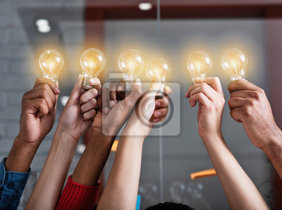 Obraz Teamwork and brainstorming concept with businessmen that share an idea with a lamp. Concept of startup