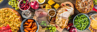Obraz Thanksgiving family dinner setting concept. Traditional Thanksgiving day food  with turkey, green beans and mashed potatoes, stuffing, pumpkin, apple and pecan pies, rustic wooden table