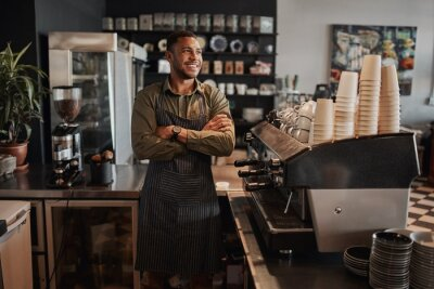 Obraz Thoughtful afro-american small coffee shop owner standing behind counter wearing apron with crossed arms looking away
