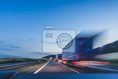 Obraz Tło fotografia autostrada. Ciężarówka na autostradzie, rozmycie ruchu, lekkie szlaki. Wieczorem lub nocy strzał ciężarówek robi logistyki i transportu na autostradzie.