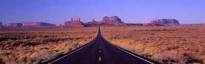 Obraz To Route 163, który biegnie przez rezerwatu Indian Navajo. Droga biegnie się w środku, a maleje w nieskończoność. Czerwone skały Monument Valley są w tle. Rośliny peeling pustyni są po obu stronach dr