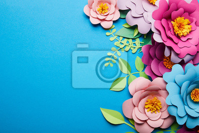 Obraz top view of colorful paper cut flowers with green leaves on blue background with copy space