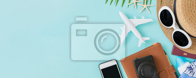 Obraz Top view of traveler accessories, tropical palm leaf and airplane on blue background with empty space for text. Travel summer holiday vacation banner concept.