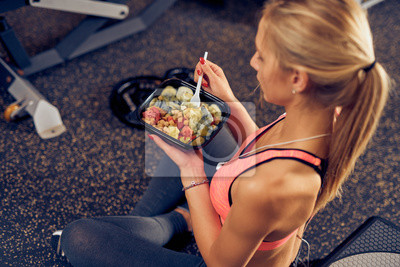 Obraz Top view of woman eating healthy food while sitting in a gym. Healthy lifestyle concept.