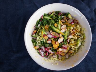 Obraz Top view on bowl with ingredients for spring vegetables salad standing on wrinkly bluish cotton fabric