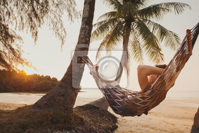 Obraz tourist relaxing in hammock on tropical beach with coconut palm trees, relaxation and leisure tourism