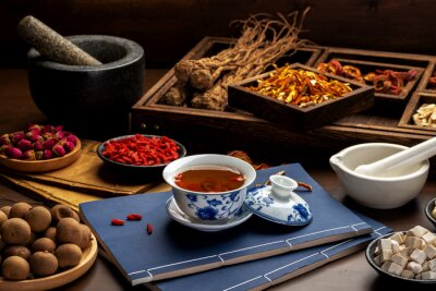 Obraz Traditional Chinese health tea and classical medical books on the table