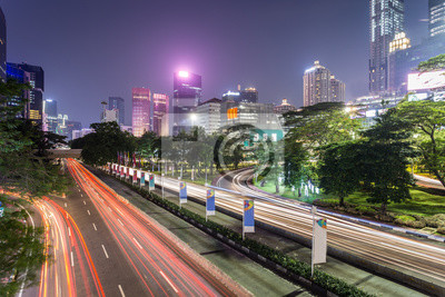 Traffic, captured with blurred motion as light trails, rush along Sudirman street in Jakarta business district