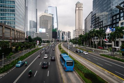Transjakarta bus drive in its dedicated traffic lane in the modern financial district of Jakarta in Indonesia capital city with an overcast sky