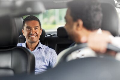 Obraz transportation, vehicle and people concept - happy smiling middle aged male passenger talking to taxi car driver