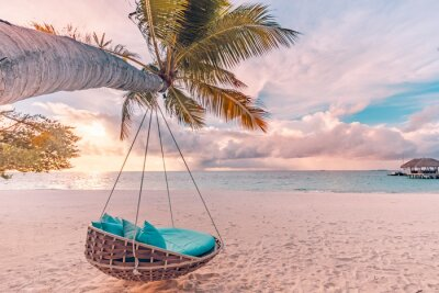 Obraz Tropical beach sunset as summer landscape with luxury resort beach swing or hammock and white sand and calm sea for sunset beach landscape. Tranquil beach scenery vacation and summer holiday concept.