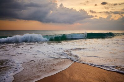 Tropical beach with crushing wave at golden sunset.