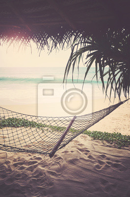 Tropical beach with hammock, retro color toning applied.