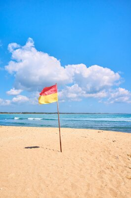 Tropical beach with red and yellow flag, Sri Lanka.