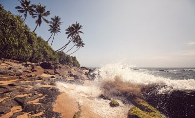 Tropical beach with wave crashing against rocks, color toning applied, Sri Lanka.
