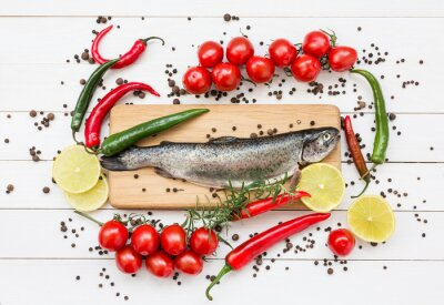 Obraz Trout fish on wooden cutting board with cherry tomatoes