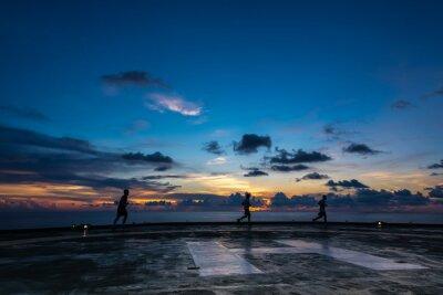 Obraz Trzech mężczyzn działa na platformie wiertniczej lądowisku w czasie zachodu słońca