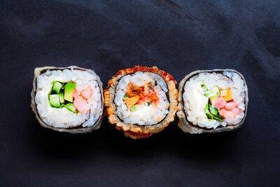Obraz Trzy kolorowe sushi na czarnym tle z copyspace