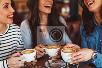Obraz Trzy młode kobiety cieszą się kawą w kawiarni