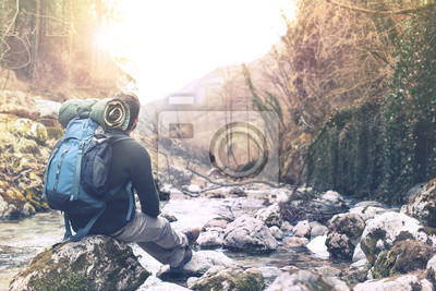 Obraz turysta mężczyzna przechodząc przez rzekę, aby dotrzeć na drugą stronę