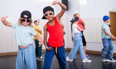Obraz Tween blonde girl and mulatto boy in caps and sunglasses dancing hip-hop in group lesson in dance school..