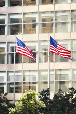 Two American Flags in front of an office building, New York City, USA.