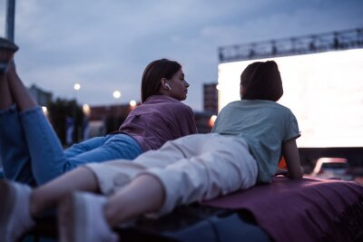 Obraz Two girls lying on the roof of a car, having fun while watching a movie in an open air cinema with a big white screen
