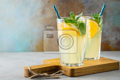 Obraz Two glass with lemonade or mojito cocktail with lemon and mint, cold refreshing drink or beverage with ice on rustic blue background. Copy space