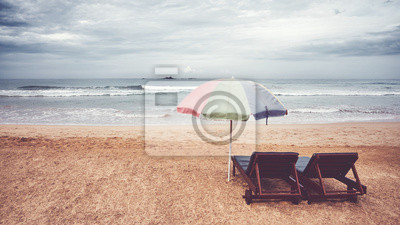 Two sunbeds and umbrella on an empty beach, color toning applied, Sri Lanka.