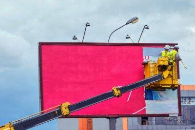 Obraz Two workers install red billboard on roadside of city street