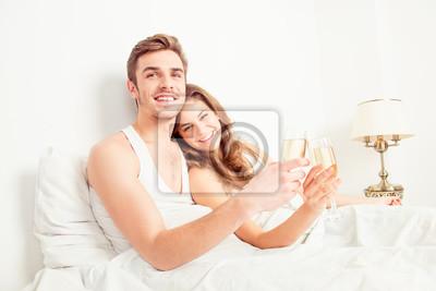 Obraz Twoje zdrowie! Szczęśliwa para zakochanych obchodzimy miesiąc miodowy w sypialni wi