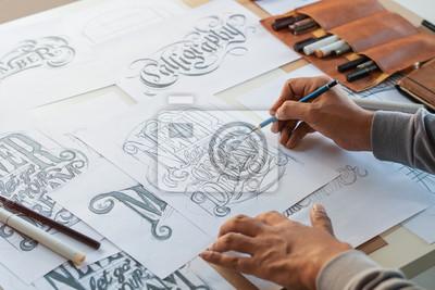 Obraz Typography Calligraphy artist designer drawing sketch writes letting spelled pen brush ink paper table artwork.Workplace design studio.