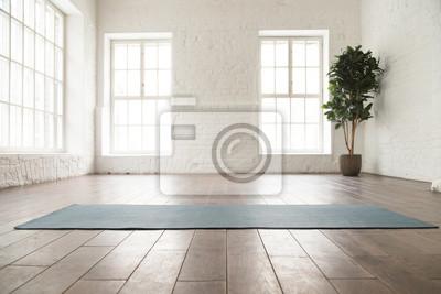 Obraz Unrolled yoga mat on wooden floor in yoga studio